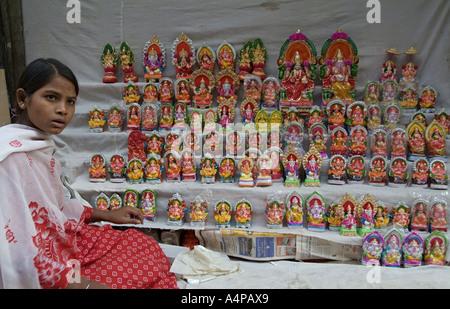 Girl selling statues of Hindu Gods in Chandni Chowk in Delhi India - Stock Photo
