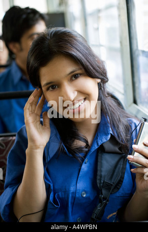 Female student listening to mp3 player on bus - Stock Photo