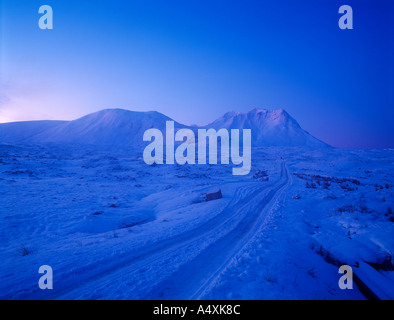 Pre dawn scene in midwinter in Glencoe Scottish Highlands with snowy track and snow covered hills - Stock Photo