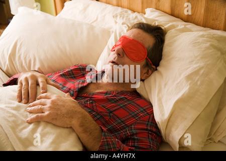 Man sleeping with eye mask - Stock Photo