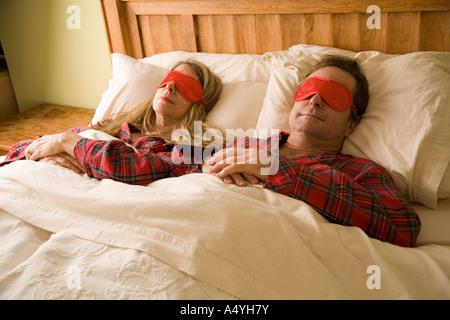 Couple sleeping with eye masks - Stock Photo