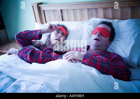 Woman peeking at man wearing eye mask - Stock Photo