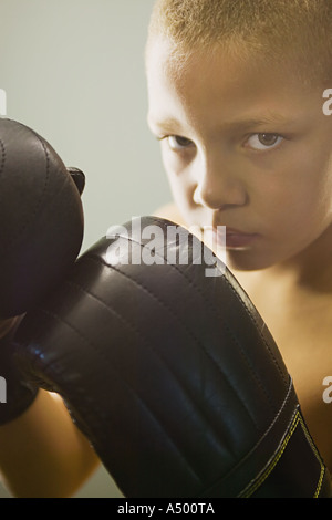 Boy wearing boxing gloves - Stock Photo