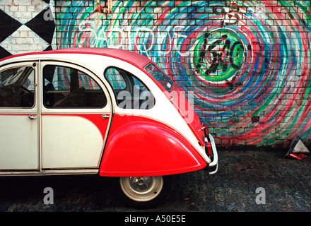 Wall graffiti and Citroen 2CV off Brick Lane in Londons East End - Stock Photo