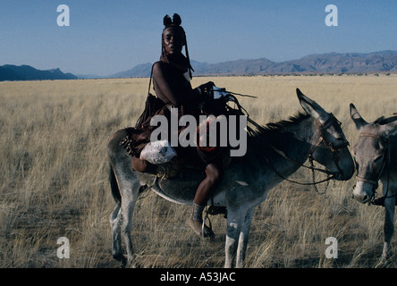Himba nomad women in traditional leather clothing crossing the Marienfluss on donkey in Kaokoland northern Namibia - Stock Photo
