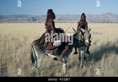 Himba women in traditional leather clothing crossing the Marienfluss on donkey in Kaokoland northern Namibia - Stock Photo