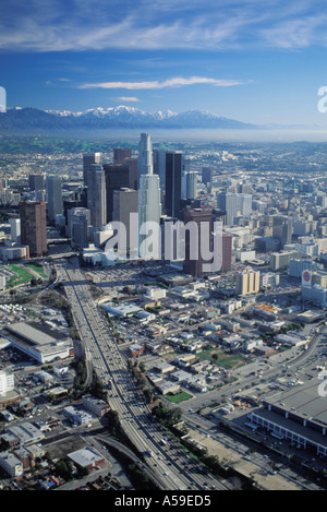 Aerial view of Los Angeles downtown Civic Center with freeways and snow on mountains - Stock Photo
