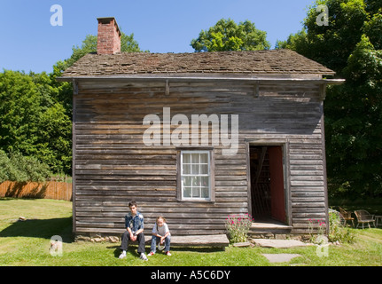 Two teenagers sitting on a bench in front of an old wooden house. - Stock Photo