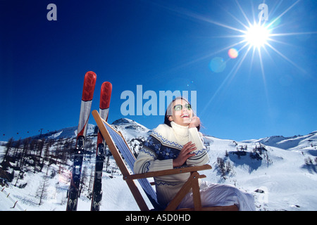 Austria, woman sitting on deckchair in snow alps, smiling, low angle view - Stock Photo