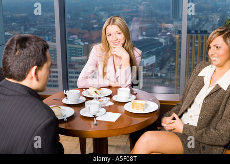 Group of People at the Cofe Table Short Depth of Focus On Woman s in the Middle Face - Stock Photo