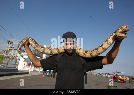 Man with pet python on the boardwalk at Coney Island - Stock Photo