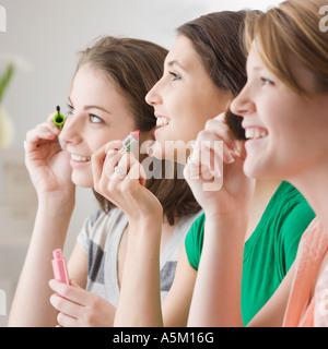 Teenage girls applying makeup - Stock Photo