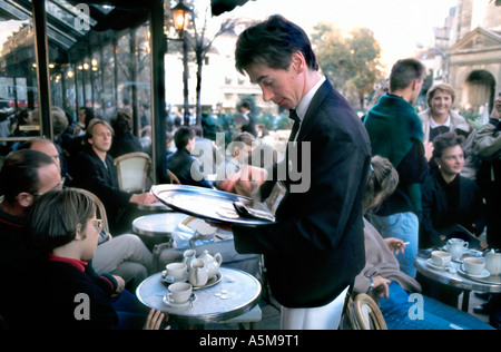 Paris France, French Café Terrace, Waiter 'Aux Deux Magots', Serving Tea to Customers at table - Stock Photo