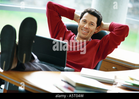 Man sitting at desk with feet up, holding laptop on lap, hands behind head - Stock Photo