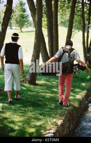Golfers looking for ball under trees, rear view - Stockfoto