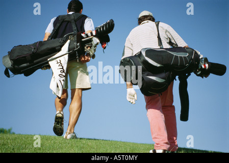Golfers carrying golf bags, rear view - Stockfoto