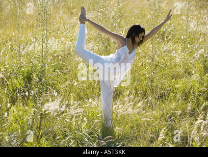Woman standing in shiva posture in field - Stock Photo