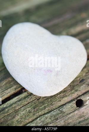 Heart-shaped stone on wood - Stock Photo