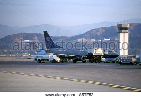 Commercial airliner being serviced at terminal. - Stock Photo