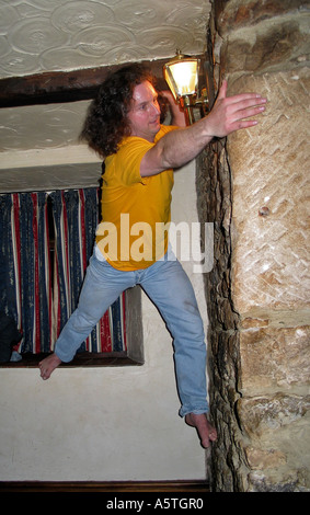 Young men indoor climbing the walls in an Inn after a few beers during a stag party weekend - Stock Photo