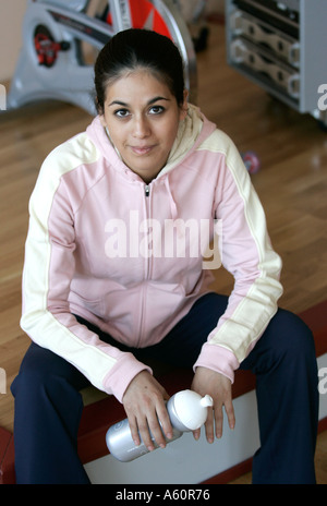 Woman holding a drink bottle having a break in fitness studio - Stockfoto
