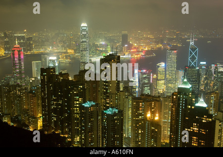 Hong Kong Island. Evening night view from Victoria Peak over city centre skyscrapers and Hong Kong Harbour to Kowloon - Stock Photo