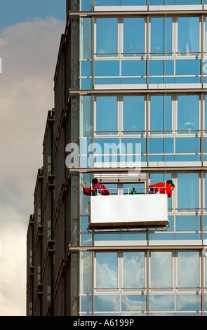 Window cleaners work on a multistoried building in Kiel, Schleswig-Holstein, Germany - Stock Photo