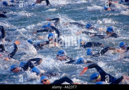 Crowd of triathletics swimming in water for triathlon - Stock Photo