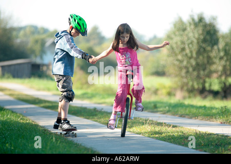 young girl riding a unicycle and pulling her brother on a skateboard - Stock Photo