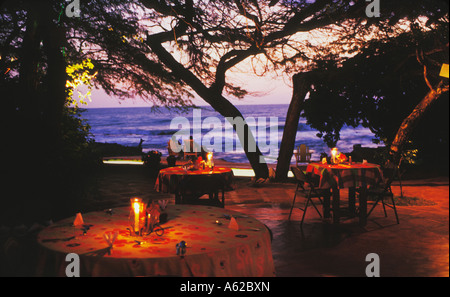 Guests watch sunset at Waterfront restaurant at Jakes Place a Hip Hideaway Resort on Treasure Beach in Jamaica - Stock Photo