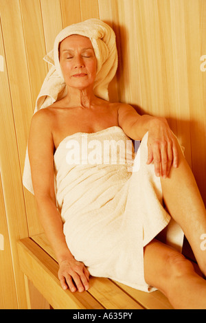 Close-up of a mature woman wearing towel sitting in a sauna - Stock Photo