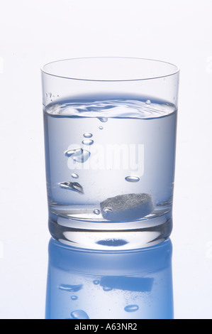 Close-up of pill and bubbles in glass of water - Stockfoto