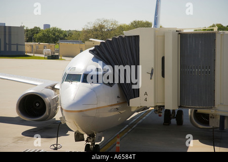 Passenger jet being serviced at the gate - Stock Photo