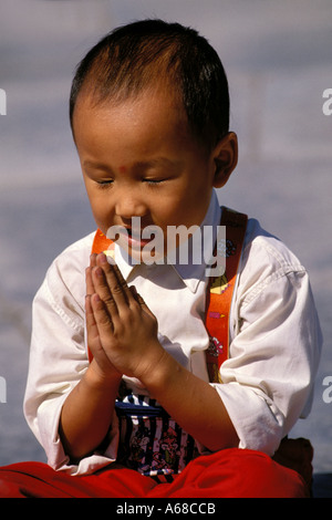 China, Beijing, Young boy with hands folded - Stock Photo