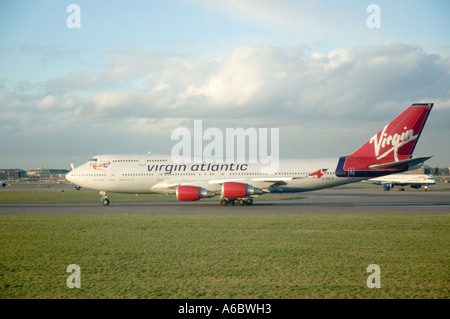 Virgin Atlantic commercial airliner taxi-ing towards the take-off runway - Stock Photo
