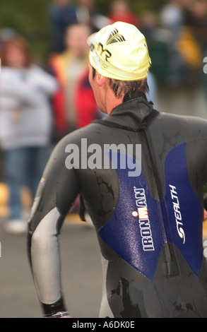 Woman out of water after finishing the swimming portion of triathlon - Stock Photo