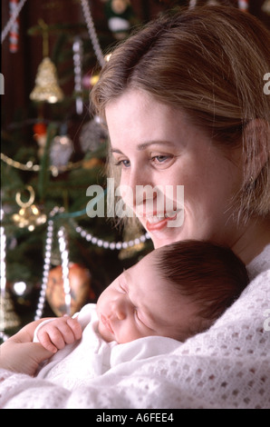 Christmas baby Essex England Twenty four 24 year old mother with five 5 week old baby boy beside Christmas tree - Stock Photo
