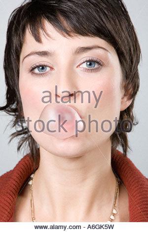 Woman blowing a bubble gum bubble - Stock Photo