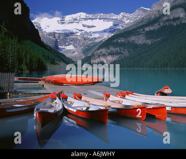 Banff National Park Canada: Red canoes on Lake Louise with Mount Victoria and Victoria Glacier in the distance - Stock Photo