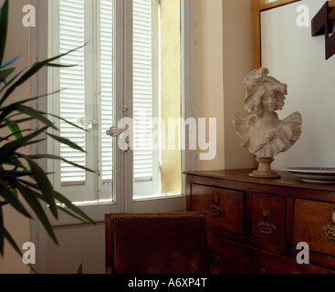 Classical marble bust on antique chest-of-drawers in front of window with exterior louvre shutters - Stockfoto