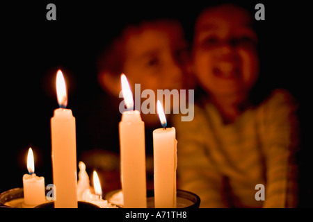 Head and shoulders colour portrait of small children in candlelight - Stock Photo