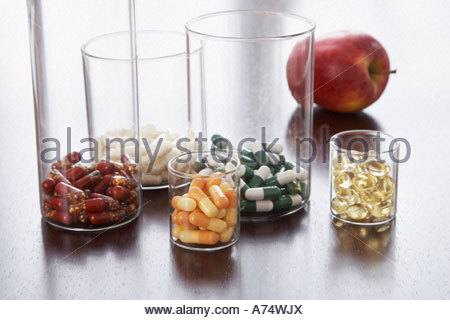 different pills and capsules in glass jars - Stock Photo