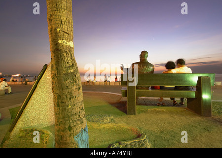 People Sitting On Bench With Statue In Manila Bay - Stockfoto