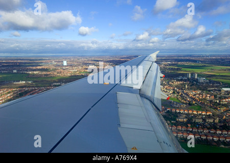 The view from a window of an aircraft over the wing as it comes in to land at London, Heathrow airport. - Stock Photo