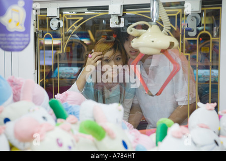 Teenage couple looking at toy grabbing game in video arcade - Stock Photo