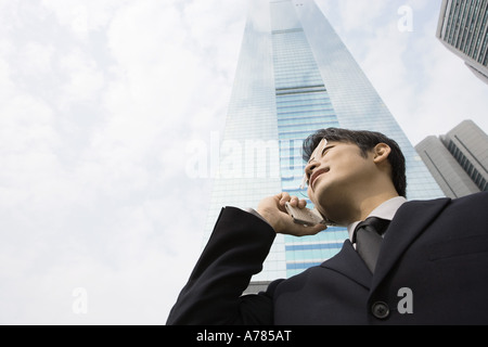 Young businessman using cell phone, skyscraper in background, low angle view - Stock Photo