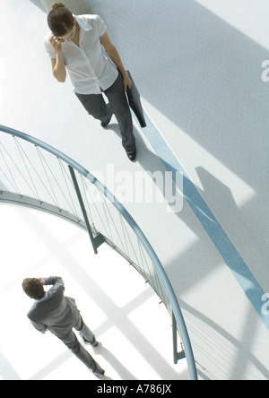 Woman using cell phone near railing, on lower floor, businessman walking by using cell phone, high angle view - Stockfoto