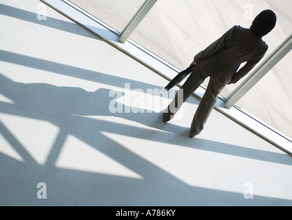Businesswoman looking out of window, full length, high angle rear view - Stock Photo