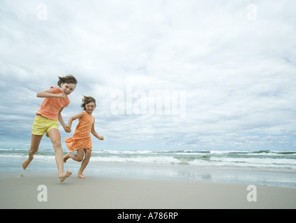 Two girls running hand in hand on beach, full length - Stock Photo