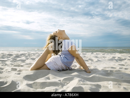 Girl doing yoga pose on beach - Stock Photo